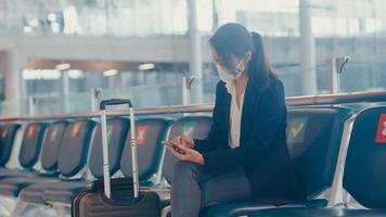 Une voyageuse d'affaires asiatique porte un costume assis avec une valise et utilise un message de chat sur un téléphone intelligent sur un banc d'attente pour le vol à l'aéroport. navetteur de voyage d'affaires dans la pandémie de covid, concept de voyage d'affaires. photo