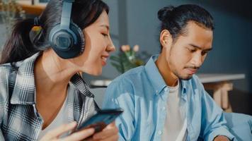 heureux jeune couple asiatique activité homme utiliser un ordinateur portable travail se détendre profiter avec des femmes porter des écouteurs utiliser un smartphone écouter de la musique au canapé dans le salon de la maison. jeune marié travail à domicile concept. photo