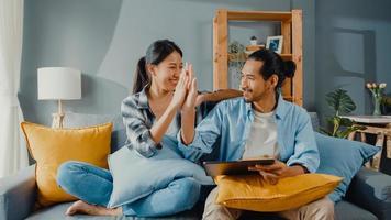 heureux jeune couple asiatique séduisant homme et femme assis sur un canapé utiliser une tablette pour acheter des meubles en ligne décorer la maison dans le salon de la nouvelle maison. concept en ligne de jeune acheteur de déménagement marié. photo