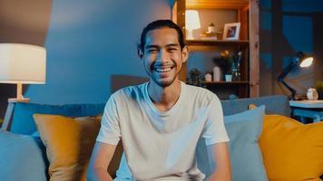 heureux jeune homme asiatique indépendant regardant la caméra sourire et parler avec des amis lors d'un appel vidéo en ligne la nuit dans le salon à la maison, rester à la maison en quarantaine, travailler à domicile, concept de distanciation sociale. photo