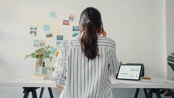 une jeune femme d'affaires asiatique appelle un téléphone portable avec des collègues de l'entreprise à propos du plan de marché du graphique des finances du travail dans un ordinateur portable et une tablette à la maison. une étudiante apprend en ligne, travaille à domicile. photo