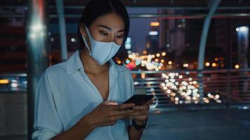 jeune femme d'affaires asiatique en vêtements de mode portant un masque facial à l'aide d'un téléphone intelligent en tapant un message texte tout en se tenant à l'extérieur dans une ville urbaine la nuit. distanciation sociale pour empêcher la propagation du concept covid-19. photo