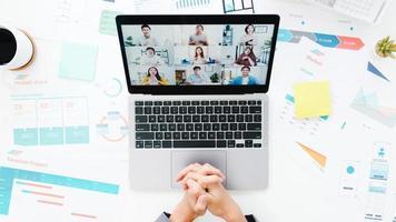 vue de dessus d'une jeune femme d'affaires asiatique utilisant un ordinateur portable parler à un collègue du plan lors d'une réunion par appel vidéo tout en travaillant à domicile dans le salon. distanciation sociale, quarantaine pour la prévention du virus corona. photo