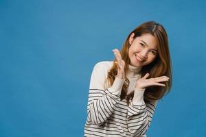 jeune femme asiatique à l'expression positive, sourit largement, vêtue d'un tissu décontracté et regarde la caméra isolée sur fond bleu. heureuse adorable femme heureuse se réjouit du succès. concept d'expression faciale. photo
