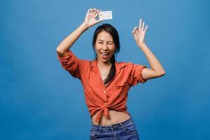 jeune femme asiatique montre une carte bancaire de crédit avec une expression positive, sourit largement, vêtue de vêtements décontractés, se sentant heureuse et isolée sur fond bleu. concept d'expression faciale. photo
