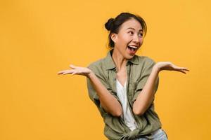 la jeune femme asiatique ressent le bonheur avec une expression positive, une joyeuse surprise funky, vêtue d'un tissu décontracté isolé sur fond jaune. heureuse adorable femme heureuse se réjouit du succès. expression faciale. photo