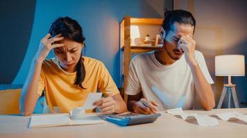 stress asie couple homme et femme utilisent la calculatrice pour calculer le budget familial, les dettes, les dépenses pendant la crise économique financière à la maison la nuit. problème d'argent de mariage, concept de plan de budget familial. photo