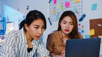 groupe d'hommes d'affaires asiatiques utilisant un ordinateur portable présentation et réunion de communication pour réfléchir à des idées sur les nouveaux collègues du projet travaillant sur la stratégie de réussite du plan dans le bureau à domicile moderne de nuit. photo