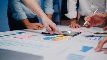 Les hommes d'affaires et les femmes d'affaires de l'Asie du millénaire se réunissant pour réfléchir à des idées sur de nouveaux collègues de projet de paperasse travaillant ensemble pour planifier une stratégie de réussite apprécient le travail d'équipe dans un petit bureau de nuit moderne. photo