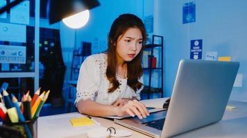 des femmes asiatiques indépendantes utilisant un ordinateur portable travaillent dur dans un nouveau bureau à domicile normal. travailler à partir de la surcharge de la maison la nuit, travail à distance, auto-isolement, distanciation sociale, quarantaine pour la prévention du virus corona. photo