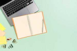 photo créative à plat du bureau de l'espace de travail. vue de dessus bureau avec ordinateur portable, tasse à café et cahier noir maquette ouverte sur fond de couleur vert pastel. vue de dessus maquette avec copie espace photographie.