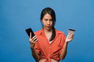 jeune femme asiatique utilisant un téléphone et une carte bancaire de crédit avec une expression négative, criant excité, pleurant émotionnellement en colère dans un tissu décontracté et se tenant isolée sur fond bleu. concept d'expression faciale. photo