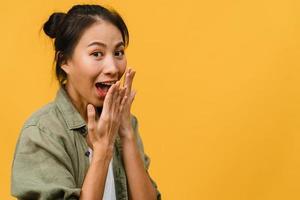 la jeune femme asiatique ressent le bonheur avec une expression positive, une joyeuse surprise funky, vêtue d'un tissu décontracté et regardant la caméra isolée sur fond jaune. heureuse adorable femme heureuse se réjouit du succès. photo