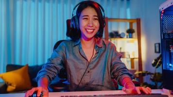 joyeuse asie professionnelle fille gamer porter casque participation jouer jeu vidéo néons colorés ordinateur dans le salon à la maison. jeu de streaming esport en ligne, concept d'activité de quarantaine à domicile. photo