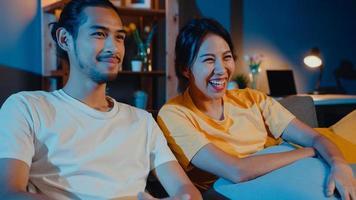 couple d'asie romantique homme et femme sourire et rire s'allonger sur le canapé dans le salon la nuit regarder un film de comédie à la télévision ensemble à la maison. couple marié mode de vie familial, concept de séjour à la maison. photo