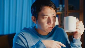 un homme d'affaires asiatique fait une pause avec une tasse de café, détendez-vous et vérifiez l'affectation de travail sur un ordinateur portable pour l'ordre du jour dans le salon à la maison les heures supplémentaires la nuit, travaillez à partir du concept de pandémie corona à domicile. photo