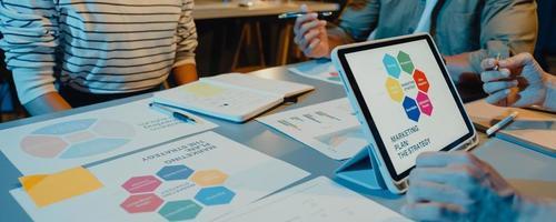 les hommes d'affaires d'asie se réunissent les statistiques d'analyse du plan de remue-méninges et l'en-tête de l'équipe tiennent le graphique de la tablette et l'employé prend note dans la nuit du bureau à domicile. fond de bannière panoramique avec espace de copie. photo