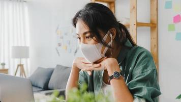 Une femme d'affaires asiatique portant un masque médical utilisant un ordinateur portable parle à ses collègues du plan lors d'un appel vidéo tout en travaillant à domicile dans le salon. distanciation sociale, quarantaine pour la prévention du virus corona. photo
