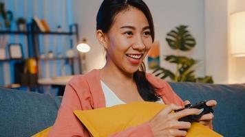 une jeune femme asiatique utilisant une manette sans fil joue à un jeu vidéo en ayant un moment heureux et amusant sur un canapé dans le salon la nuit à la maison. rester à la maison, activité d'auto-quarantaine pour la quarantaine covid ou coronavirus. photo