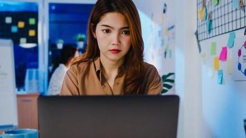 heureuse femme d'affaires d'asie distanciation sociale dans une nouvelle situation normale pour la prévention des virus tout en utilisant des heures supplémentaires d'affaires en ligne pour ordinateur portable au travail la nuit au bureau. vie et travail après le coronavirus. photo