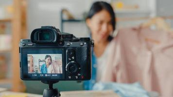 jeune créatrice de mode asiatique utilisant un téléphone portable recevant un bon de commande et montrant des vêtements enregistrant une vidéo en direct en ligne avec une caméra. propriétaire de petite entreprise, concept de livraison de marché en ligne. photo
