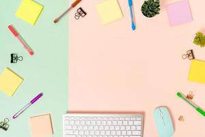espace de travail minimal - photo créative à plat du bureau de l'espace de travail. bureau vue de dessus avec clavier, souris et note adhésive sur fond de couleur rose vert pastel. vue de dessus avec copie espace photographie.