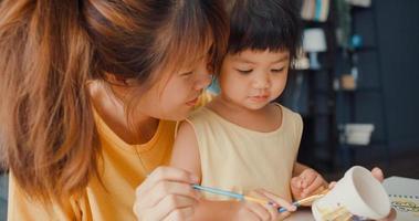 Joyeuse famille asiatique joyeuse, maman enseigne à une fille en bas âge peindre un pot en céramique s'amusant à se détendre sur une table dans le salon de la maison. passer du temps ensemble, distance sociale, quarantaine pour la prévention des coronavirus. photo