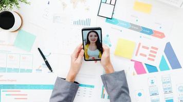 vue de dessus d'une jeune femme d'affaires asiatique utilisant un téléphone pour parler à un collègue du plan lors d'une réunion par appel vidéo tout en travaillant à domicile dans le salon. distanciation sociale, quarantaine pour la prévention du virus corona. photo