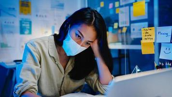 les femmes asiatiques indépendantes portent un masque facial en utilisant un ordinateur portable pour travailler dur dans un nouveau bureau normal. travail à domicile surchargé la nuit, auto-isolement, distanciation sociale, quarantaine pour la prévention du virus corona. photo