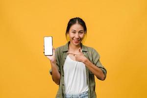 une jeune femme asiatique montre un écran de smartphone vide avec une expression positive, sourit largement, vêtue de vêtements décontractés, se sentant heureuse sur fond jaune. téléphone portable avec écran blanc en main féminine. photo