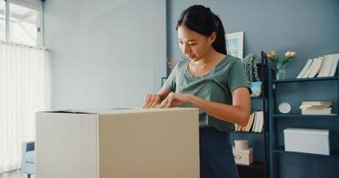 Heureuse belle dame asiatique déballant le colis de livraison en carton du marché en ligne dans le salon de la maison. acheteur satisfait dans les produits de déballage sur Internet, les achats en ligne et le concept de livraison. photo