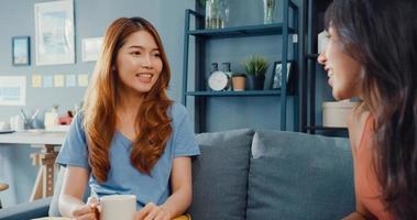 femmes au foyer asiatiques avec détente décontractée sur un canapé avec une tasse de thé parlent ensemble de leur vie et des potins de la relation mari dans le salon de la maison. Les colocataires des amies restent ensemble dans un dortoir. photo
