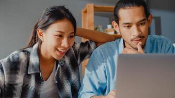 succès asie jeune couple homme et femme ravis enthousiasmés accord de prêt bancaire maready pour une nouvelle maison en ligne dans un ordinateur portable à la maison, mari et femme heureux heureux de l'investissement financier bonne nouvelle. photo