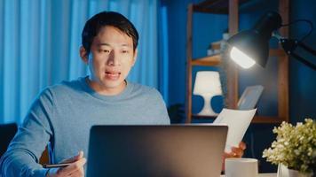 un jeune homme d'affaires asiatique se concentre sur la tâche de réunion d'appels vidéo en ligne sur la paperasse avec un collègue dans un ordinateur portable dans le salon à la maison des heures supplémentaires la nuit, travail à partir du concept de pandémie corona à domicile. photo