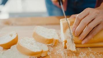 mains de jeune femme asiatique chef tenant un couteau coupant du pain de grains entiers sur une planche de bois sur une table de cuisine dans la maison. production de pain frais fait maison, alimentation saine et concept de boulangerie traditionnelle. photo