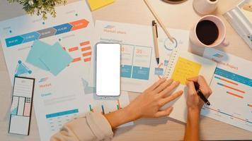 vue de dessus d'une jeune femme d'asie indépendante utiliser un téléphone avec un écran blanc vierge pour afficher du texte publicitaire et écrire une feuille de calcul financière graphique de compte plan de marché la nuit au bureau. clé chroma. photo