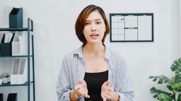 femme d'affaires asiatique distanciation sociale dans une nouvelle situation normale pour la prévention des virus en regardant la présentation de la caméra à des amis sur le plan en appel vidéo pendant le travail au bureau. mode de vie après le virus corona. photo