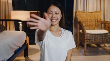 joyeuse jeune femme asiatique vlogger regarde la caméra à l'aide d'un téléphone portable passe un appel vidéo en direct sur un canapé dans le salon la nuit à la maison. distanciation sociale, quarantaine pour le coronavirus. vue en gros plan de la webcam. photo