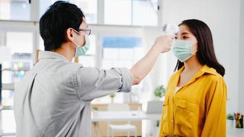 un réceptionniste asiatique portant un masque protecteur utilise un vérificateur de thermomètre infrarouge ou un pistolet à température sur le front du client avant d'entrer dans le bureau. mode de vie nouveau normal après le virus corona. photo