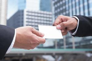 mains de deux hommes d'affaires donnant une carte de visite vide photo