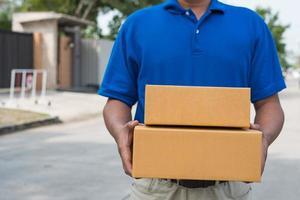 livreur bleu tenant une boîte en carton de colis. photo