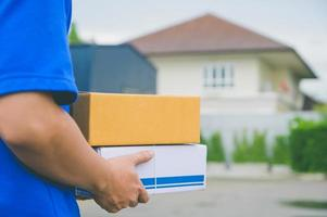gros livreur en uniforme bleu tenant une boîte en carton de colis. photo