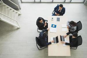 vue de dessus de l'équipe de gens d'affaires asiatiques analysant les statistiques financières. vue en grand angle d'une équipe d'hommes d'affaires réunion conférence discussion concept d'entreprise au bureau. photo