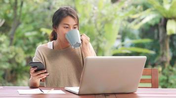 femme asiatique indépendante travaillant à la maison, femme d'affaires travaillant sur ordinateur portable et utilisant un téléphone portable buvant du café assis sur une table dans le jardin le matin. femmes de style de vie travaillant à la maison concept. photo