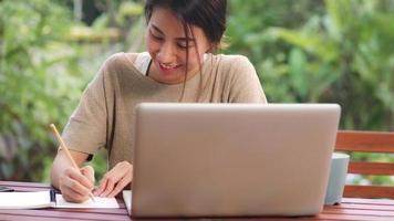 femme asiatique indépendante travaillant à la maison, femme d'affaires travaillant sur ordinateur portable assise sur une table dans le jardin le matin. femmes de style de vie travaillant à la maison concept. photo