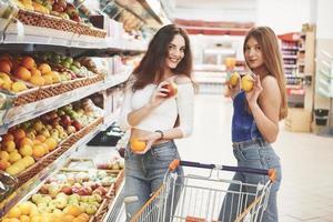 deux femmes choisissent des fruits de saison dans l'épicerie du supermarché photo