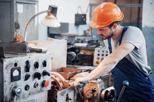 portrait d'un jeune travailleur portant un casque de sécurité dans une grande usine métallurgique. l'ingénieur sert les machines et fabrique des pièces pour les équipements à gaz photo