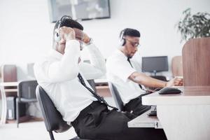opérateur de support client afro-américain avec casque mains libres travaillant au bureau photo