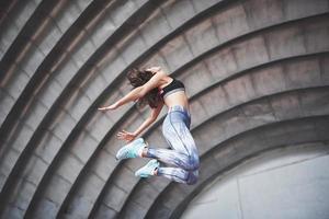 une belle brune athlète effectue des exercices en plein air photo