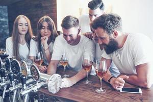 concept de loisirs et de communication. groupe d'amis souriants heureux appréciant des boissons et parlant au bar ou au pub photo